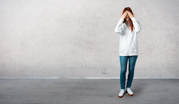 Junges rothaarigemädchen in einem städtischen weißen sweatshirt mit den gläsern, die augen durch hände bedecken
