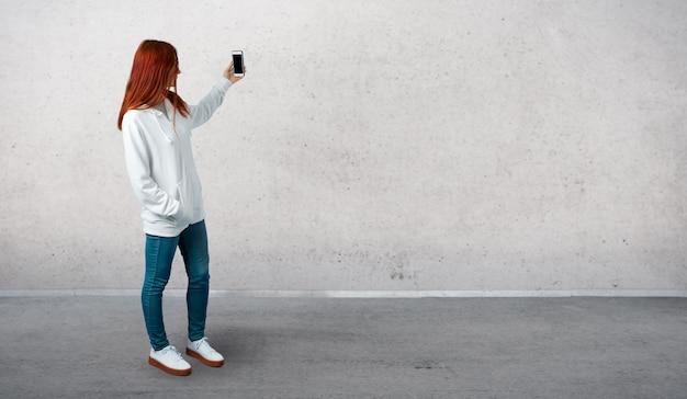Junges rothaarigemädchen in einem städtischen weißen sweatshirt mit gläsern ein selfie mit dem mobile nehmend