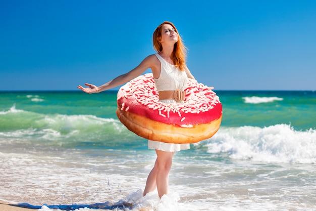 Junges rothaarigemädchen mit donut an der taille