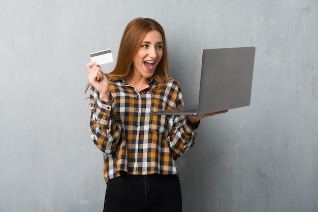 Junges rothaarigemädchen über schmutzwand mit laptop und kreditkarte