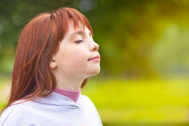 Junges rothaariges mädchen atmet luft im park ein. nettes kleines mädchen ruht in der natur an der frischen luft.