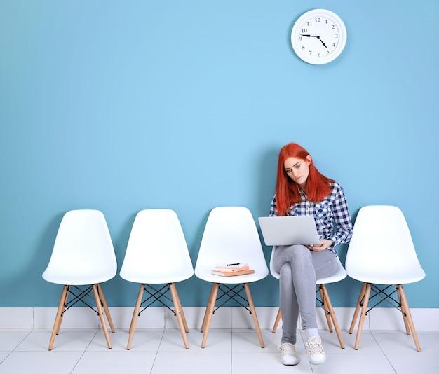 Junges rothaariges mädchen, das auf einem stuhl sitzt und laptop in der blauen halle verwendet