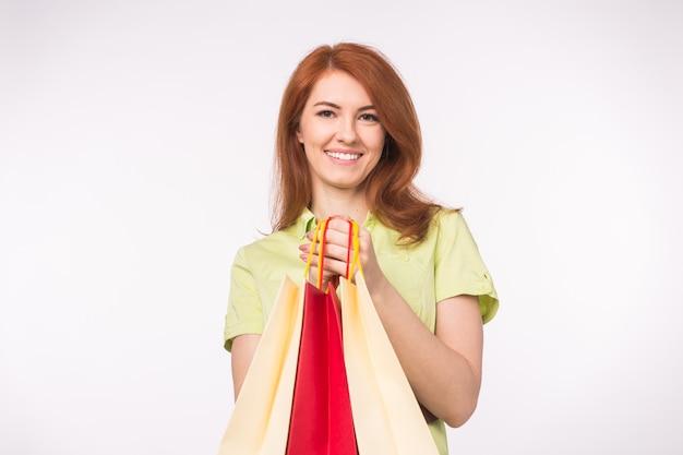Junges rothaariges mädchen, das viele einkaufstaschen hält.