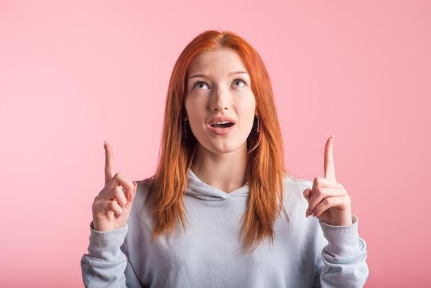 Junges rothaariges mädchen, das zeigefinger oben im studio auf einem rosa hintergrund zeigt