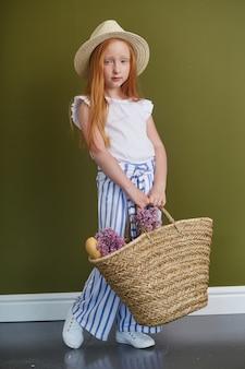 Junges rothaariges mädchen in einem strohhut mit dem langen schönen haar und den großen blauen augen