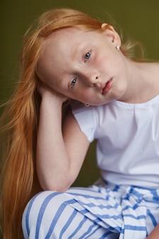Junges rothaariges mädchen mit dem langen schönen haar und den großen blauen augen