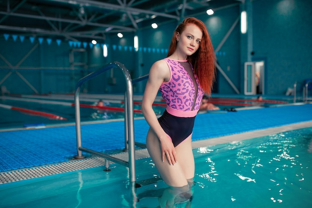 Junges rothaariges mädchen steht im swimmingpool