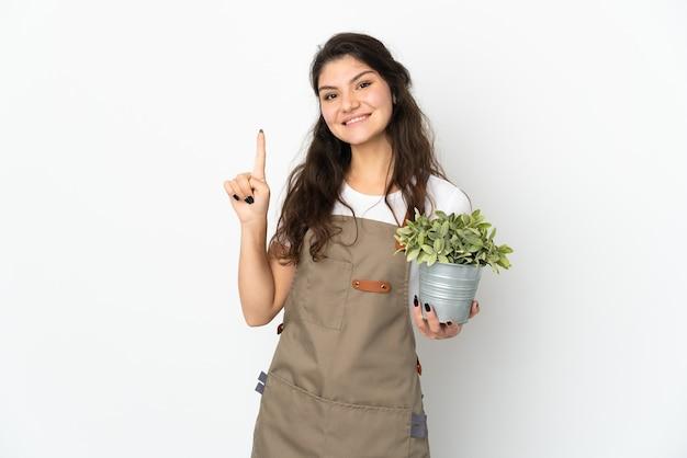 Junges russisches gärtnermädchen, das eine isolierte pflanze hält, die einen finger im zeichen des besten zeigt und hebt