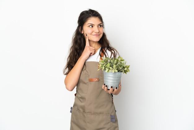 Junges russisches gärtnermädchen, das eine pflanze lokalisiert hält, die eine idee beim nachschlagen denkt