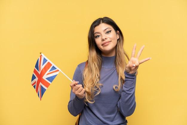 Junges russisches mädchen, das eine flagge des vereinigten königreichs lokalisiert auf gelbem hintergrund glücklich hält und drei mit den fingern zählt