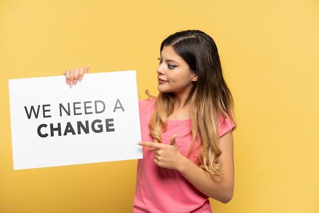 Junges russisches mädchen isoliert auf gelbem hintergrund, das ein plakat mit dem text we need a change hält und darauf zeigt