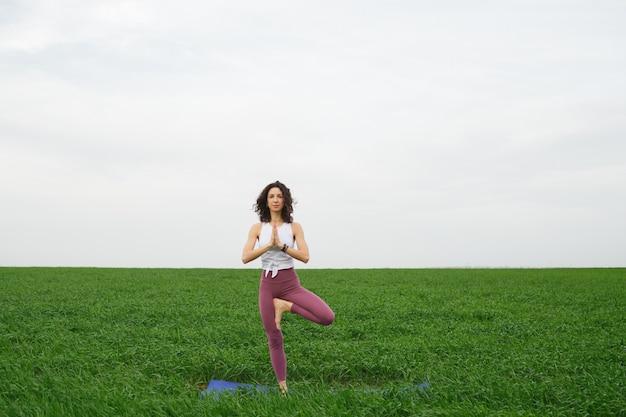Junges schlankes mädchen, das yoga im freien in einem grünen feld tut