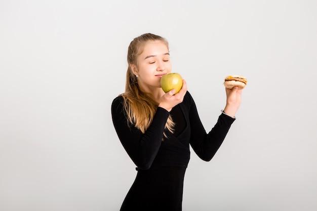 Junges schlankes mädchen hält einen hamburger und einen apfel. wählen sie gesundes essen, kein fast food