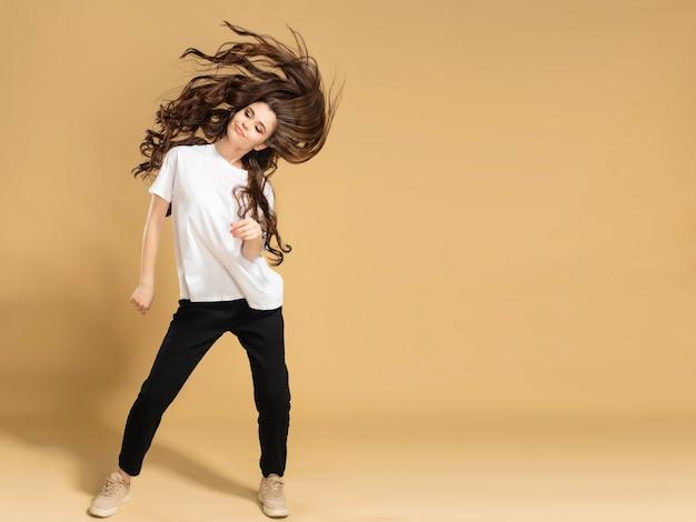 Junges schlankes mädchen in einem weißen t-shirt, das langes haar auf einer pastellorange tanzt und winkt.