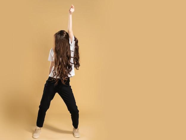 Junges schlankes mädchen in einem weißen t-shirt mit einem geschlossenen gesicht und langen tanzenden haaren, die ihre hand auf eine pastellorange erheben.