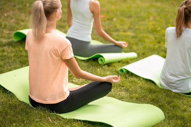Junges schlankes mädchen sitzt entspannt im lotussitz und macht an einem warmen tag mit anderen mädchen auf grünem gras im park übungen auf yogamatten. .