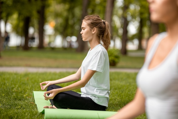 Junges schlankes mädchen sitzt im lotussitz mit geschlossenen augen und macht an einem warmen tag übungen mit anderen mädchen auf grünem gras im park. .