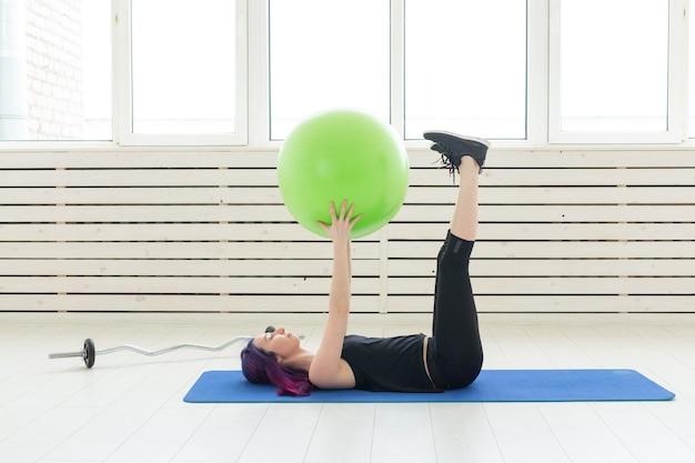 Junges schlankes mädchen trainiert und streckt sich auf einem grünen fitball in der hellen turnhalle