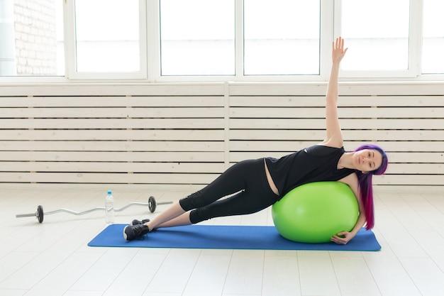Junges schlankes mädchen trainiert und streckt sich für den rücken auf einem grünen fitball im hellen fitnessstudio. gesundes rücken- und bandkonzept