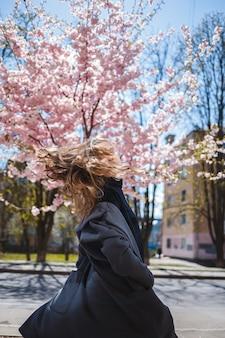 Junges schlankes weibliches model mit langen, gewellten haaren und in einem grauen mantel, turnschuhen, die sich auf der straße drehen. frühlingsblütenbäume frau mädchen lacht und rennt, um sich zu freuen. selektiver fokus