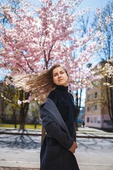 Junges schlankes weibliches model mit langen, gewellten haaren und in einem grauen mantel, turnschuhen, die sich auf der straße drehen. frühlingsblütenbäume frau mädchen lacht und rennt, um sich zu freuen