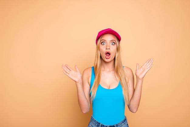 Junges schockiertes blondes mädchen, das lässige sommerkleidung trägt