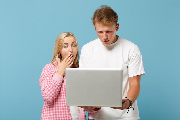 Junges schockiertes paar zwei freunde mann und frau in weißen rosa leeren leeren t-shirts posieren