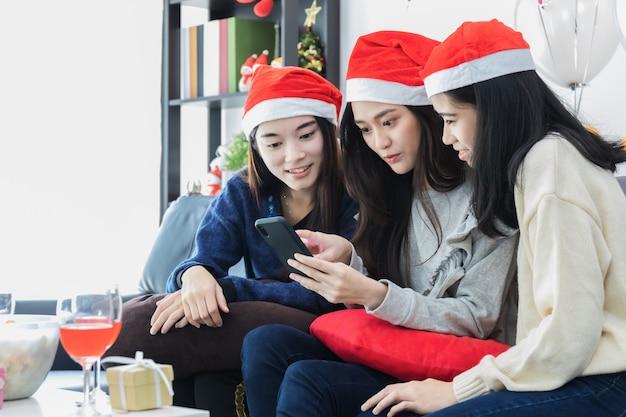 Junges schönes asiatin selfie mit smartphone und feier mit bestem freund lächelndes gesicht im raum mit weihnachtsbaumdekoration für feiertagsfestival weihnachtspartei und feierkonzept.