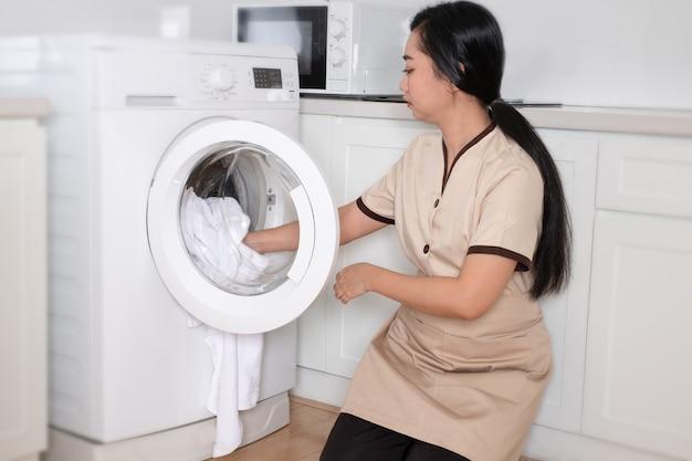 Junges schönes asiatisches dienstmädchen, das die weiße kleidung der waschmaschine im hotelzimmer lädt