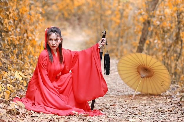 Junges schönes asiatisches frauenkleid im traditionellen chinesischen altmodischen kriegerstil mit altem wort und regenschirm. nette frau im roten kleid sitzend und im freien.
