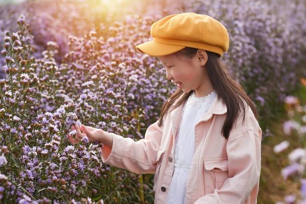 Junges schönes asiatisches mädchenkind, das blume beobachtet und im lila blumenfeld lächelt.