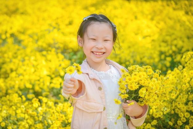 Junges schönes asiatisches mädchenkind, das blume hält und im gelben chrysanthemenfeld lächelt.