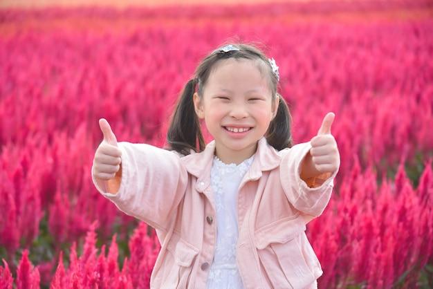 Junges schönes asiatisches mädchenkind, das lächelt und daumen oben im roten blumenfeld zeigt.