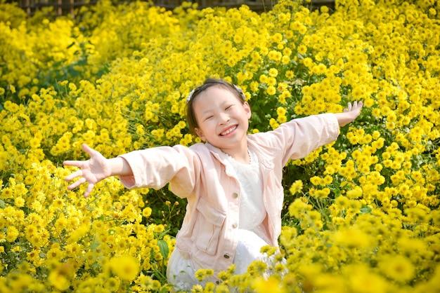 Junges schönes asiatisches mädchenkind, das lächelt und hände oben im gelben chrysanthemenfeld erhebt.