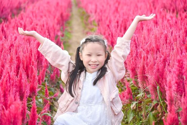 Junges schönes asiatisches mädchenkind, das lächelt und hände oben im roten blumenfeld erhebt.