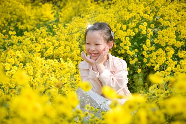 Junges schönes asiatisches mädchenkind, das sitzt und im gelben chrysanthemenfeld lächelt.