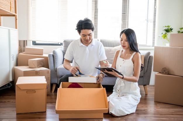 Junges schönes asiatisches paar in der liebe, die in neues zuhause zieht, auf dem boden sehr glücklich und fröhlich für neue wohnung um pappkartons sitzend hält und pappkartons hält, während sie nach hause zieht