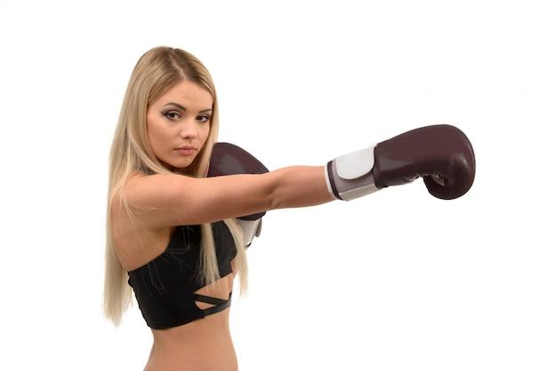 Junges schönes blondes boxmädchen, das mit handschuhen aufwirft