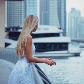 Junges schönes blondes frauenporträt bei dubai marina mit wolkenkratzern
