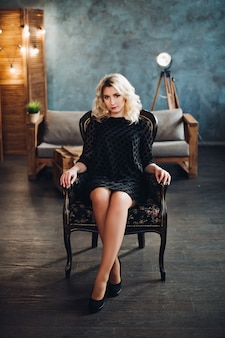 Junges schönes blondes mädchen, das im schwarzen kleid, in den hohen absätzen sitzen auf stuhl im luxusinnenraum und im betrachten der kamera trägt. heiße frau mit voluminösem haar und professionellem make-up. konzept der mode.