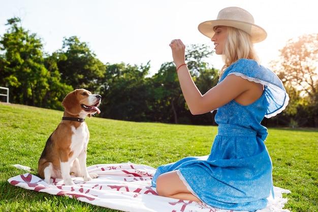 Junges schönes blondes mädchen, das mit beagle-hund im park spielt.