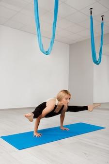 Junges schönes blondes mädchen, das yoga im fitnessstudio praktiziert.