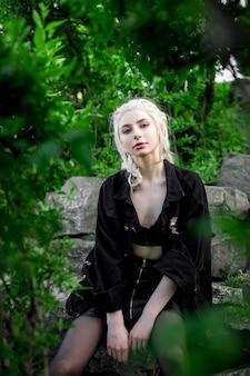 Junges schönes blondes mädchen in einer schwarzen jeansjacke natur