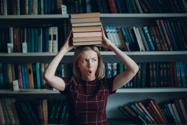 Junges schönes blondes studentinnenmädchen mit stapelbüchern