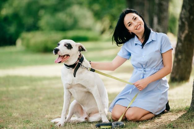 Junges schönes brünettes fröhliches mädchen im blauen kleid haben spaß und spielen mit ihrem männlichen weißen hund im freien an der natur. gut aussehende frau liebt freundliches haustier.