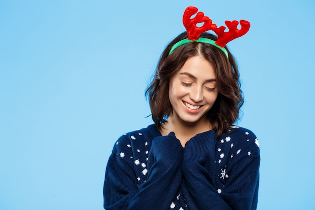 Junges schönes brünettes mädchen im gestrickten pullover und im weihnachtsrentiergeweih, die über blaue wand lächeln
