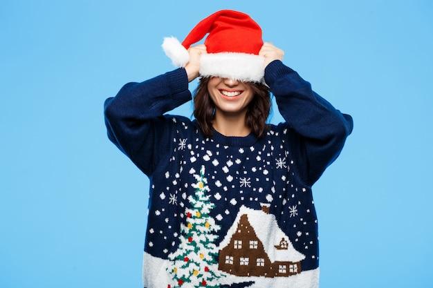 Junges schönes brünettes mädchen im gestrickten pullover und in der weihnachtsmütze, die über blaue wand lächeln