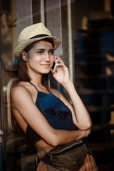 Junges schönes brünettes mädchen im hut lächelnd, am telefon sprechend.