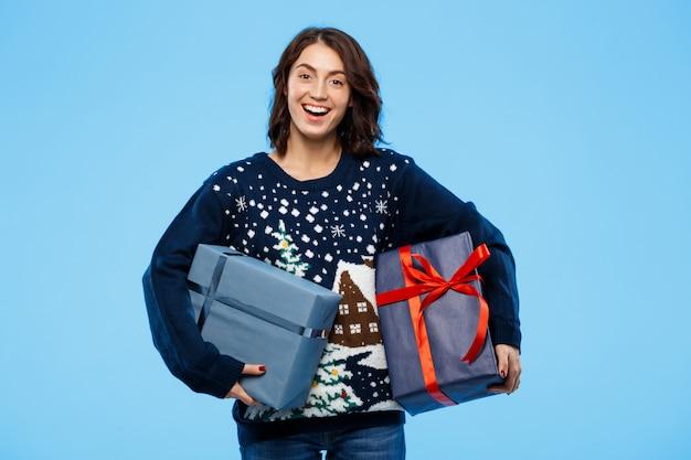 Junges schönes brünettes mädchen im kuscheligen strickpullover lächelnd, der geschenkboxen über blauer wand hält