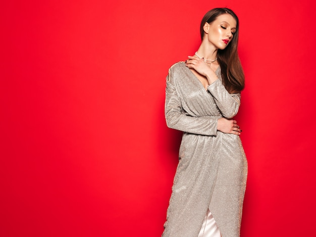 Junges schönes brünettes mädchen im schönen trendigen sommerkleid. sexy sorglose frau, die nahe rote wand im studio aufwirft. modisches modell mit hellem abendmake-up